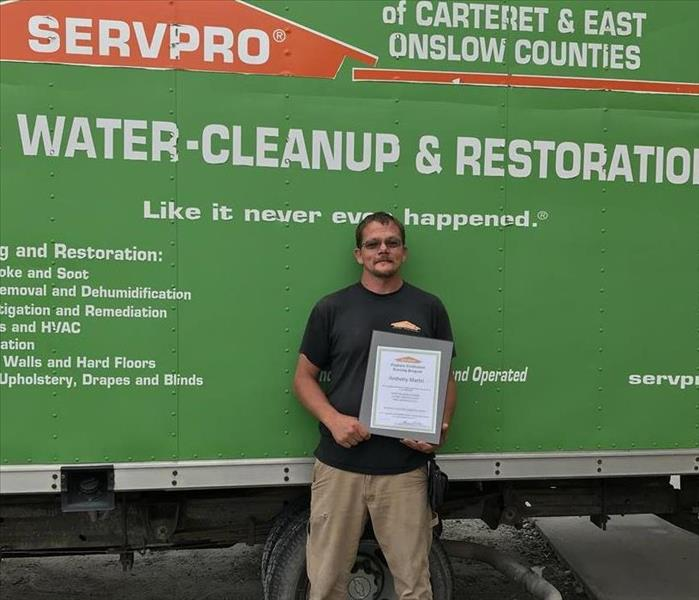 Male standing in front of green vehicle holding certificate