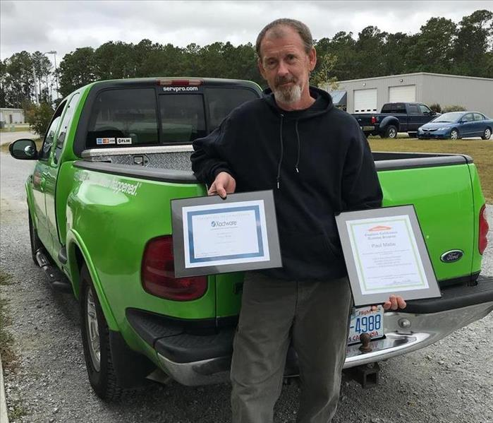 male employee holding two certificates